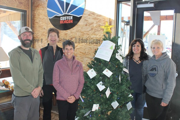 The Select-A-Gift trees are up around the community again, giving Custer residents a chance to buy a gift for a child, mom or dad who otherwise may not receive a gift this Christmas. The Custer Beacon is among the locations where trees are located. From left are Custer Beaon manager Jason Deuhr and Select-A-Gift volunteers Cheryl Schreier, Juli Ames-Curtis, Juliann Gramkow and Ione Fejfar.
