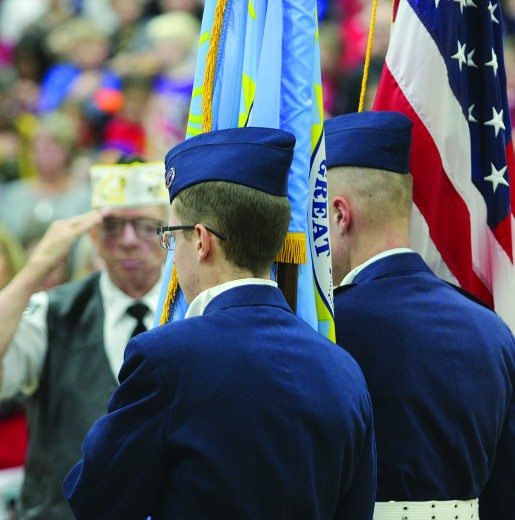 Former Custer VFW commander Jim Hattervig salutes as the Civil Air Patrol retrieves the colors at the Custer School's 25th annual Veterans Day program at the Armory on Monday afternoon.